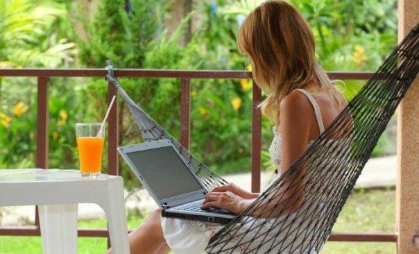 Девушка работает на компьютере на гамаке возле стола