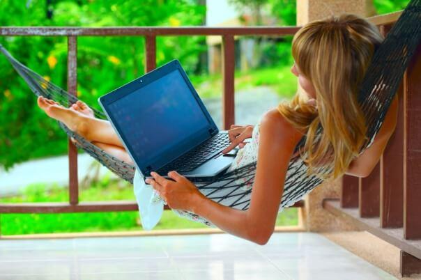 Девушка работает в гамаке с компьютером в Интернете
