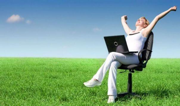 Девушка работает на компьютере среди зеленого луга