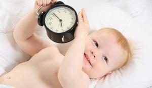 Малыш улыбается в кроватке и показывает будильник